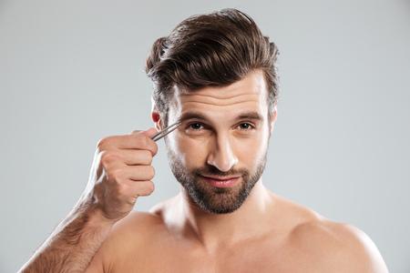Bearded young man tweezering his eyebrows isolated over grey background