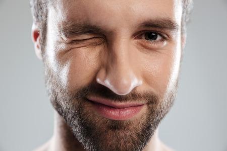 Image recadrée d'un homme barbu face à un clin d'oeil isolé sur fond blanc Banque d'images
