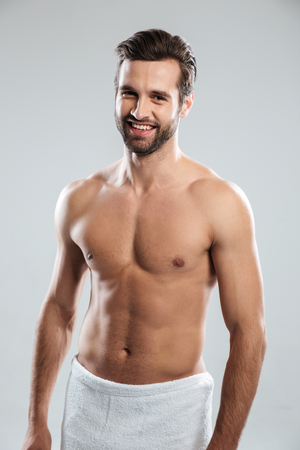 Image of happy young man dressed in towel standing isolated over grey background. Looking at camera.