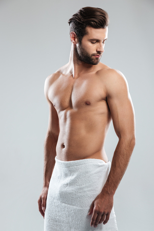 Photo of handsome young man dressed in towel standing isolated over grey background. Looking aside. Stock Photo