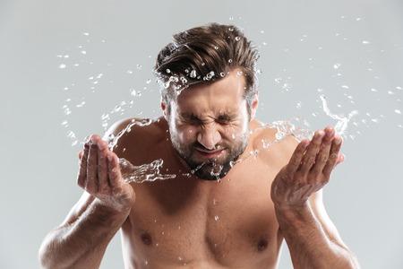 La imagen del hombre joven que se coloca aislado sobre fondo gris lava la cara. Foto de archivo - 79922386
