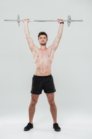 Full length portrait of a young healthy man athlete doing exercises with barbell isolated over white background