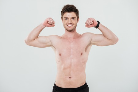 toothy: Smiling shirtless sportsman showing biceps and looking at camera isolated over white