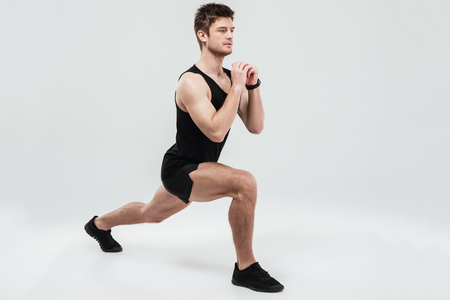 koncentrovaný: Portrét mladého koncentrovaného muže dělá dřepy cvičení izolovaných na bílém pozadí