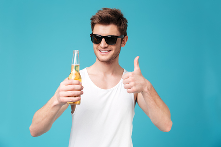 looking aside: Photo of young happy man standing over blue isolated background holding beer showing thumbs up. Looking aside.