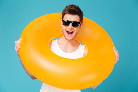 Portrait of a happy cheerful man in sunglasses holding inflatable ring isolated over blue background Stock Photo