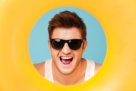 Portrait of young handsome man in sunglasses and white t-shirt looking out of the yellow swimming circle with opened mouth isolated over blue