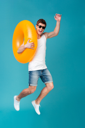 Full length portrait of a happy excited man in sunglasses holding inflatable ring and jumping isolated over blue background Фото со стока