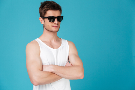 Confident handsome man in sunglasses standing with arms folded isolated over blue background