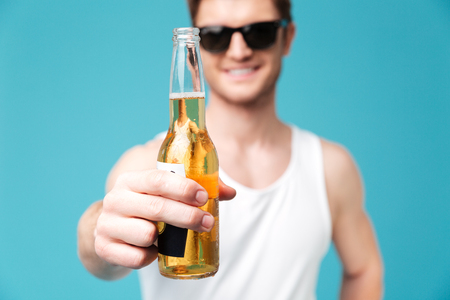 concentrate: Image of young smiling man standing over blue isolated background drinking beer. Looking at camera. Focus on beer.