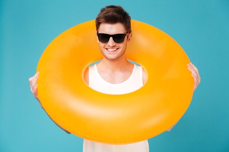Smiling funny guy in sunglasses looking through inflatable ring isolated over blue background