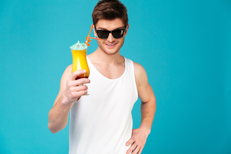 concentrate: Young handsome brunette man in sunglasses showing cocktail isolated over blue