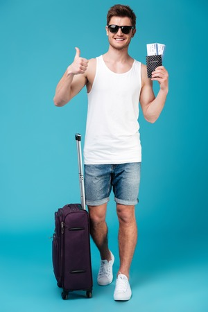 concentrate: Photo of young smiling man standing over blue isolated background near suitcase holding tickets and showing thumbs up. Looking at camera.