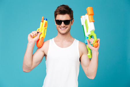 concentrate: Positive young handsome brunette man in sunglasses looking camera and holding two water guns isolated over blue