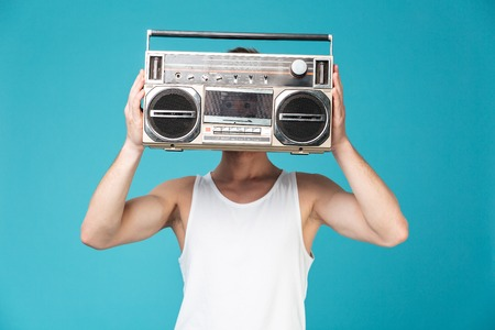 Photo of young man standing over blue isolated background covering face with tape recorder. Stock Photo