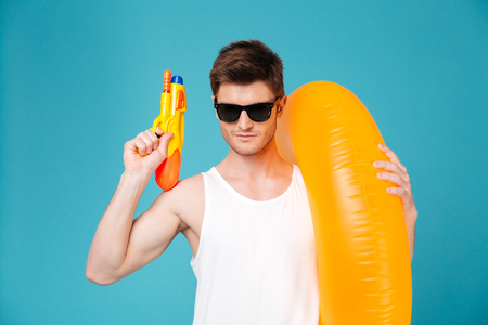 Young summer man in sunglasses holding water gun and inflatable ring isolated over blue background