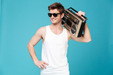 Image of young happy man standing over blue isolated background holding tape recorder. Looking aside. Imagens