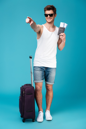 looking aside: Picture of young handsome man standing over blue isolated background near suitcase holding tickets and pointing.
