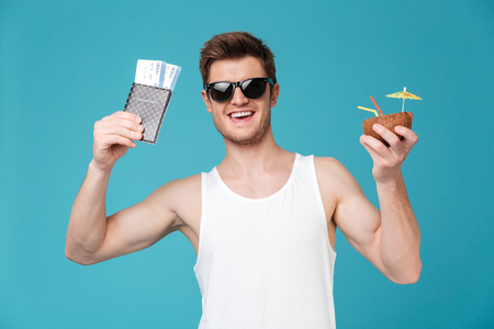 concentrate: Picture of young happy man standing over blue isolated background. Looking at camera drinking cocktail holding tickets.