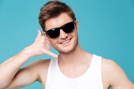 선글라스와 t- 셔츠를 입고 젊은 갈색 머리 남자의 초상화 대신 손을 잡고 파란색 통해 격리 된 스마트 폰