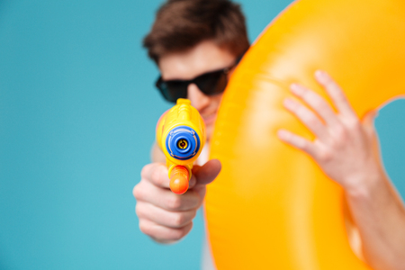 Cheerful young man in sunglasses holding inflatable ring and pointing water gun at camera isolated over blue background