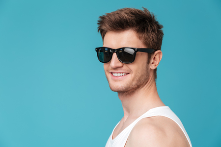 Picture of young cheerful man standing over blue isolated background. Looking at camera.