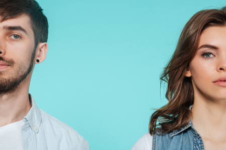 Image of serious concentrated young man standing with his sister isolated over blue background. Looking at camera.