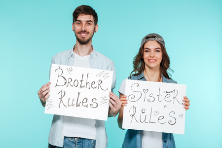 nameplate: Young handsome brother and pretty sister holding funny nameplates over blue