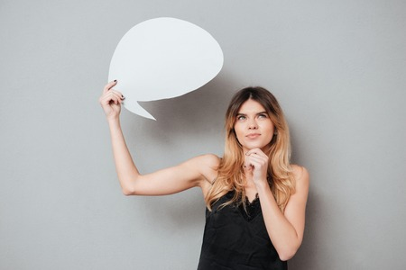 Portait of a pretty thoughtful girl holding speech bubble isolated over grey background Stok Fotoğraf