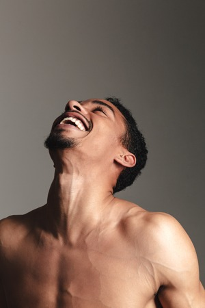looking aside: Picture of young laughing african man isolated over grey background. Looking aside.