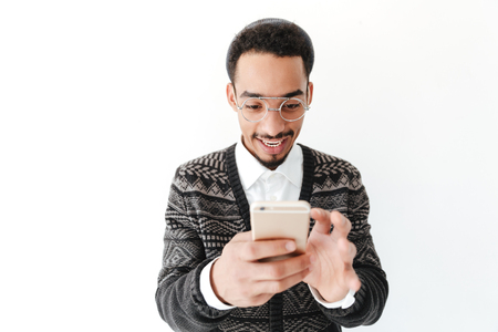 looking aside: Picture of happy young african man isolated over white background. Looking aside chatting by phone. Stock Photo