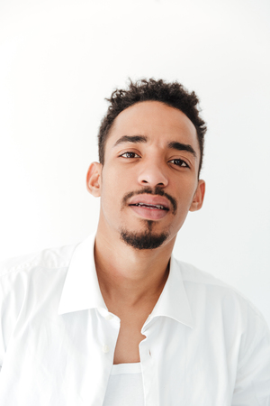 koncentrovaný: Obrázek vážný mladý african muž izolované nad bílým pozadím. Při pohledu na fotoaparát.