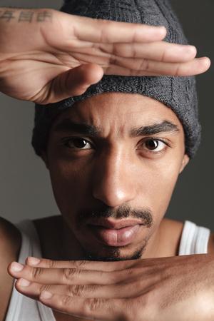 koncentrovaný: Obrázek mladý pohledný african muž izolované nad šedým pozadím. Při pohledu na fotoaparát. Reklamní fotografie