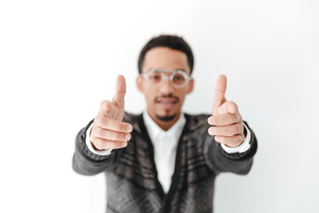 thrilled: Image of handsome young african man isolated over white background. Looking at camera pointing. Focus on hands.