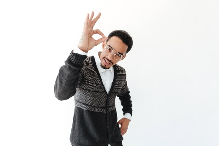Picture of handsome young african man isolated over white background. Looking at camera showing okay gesture. photo