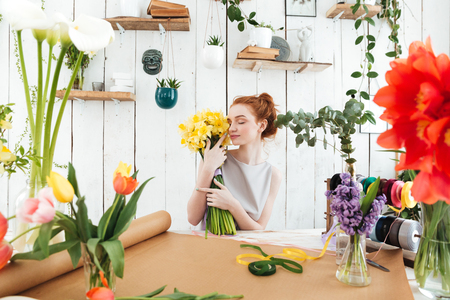 Young redhead woman florist holding flowers while making bouquet with yelllow flowers in workshop Stok Fotoğraf - 80197774