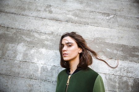 koncentrovaný: Fotografie nádherné mladé ženy stojící a představující venku. Při pohledu na fotoaparát.