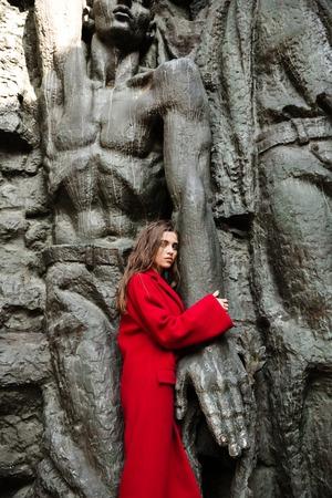 koncentrovaný: Fotografie vážné mladé ženy stojící a představující venku. Při pohledu na fotoaparát.