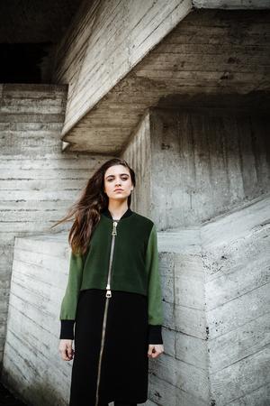 koncentrovaný: Fotografie módní hezká mladá žena stojící a představující venku. Při pohledu na fotoaparát.