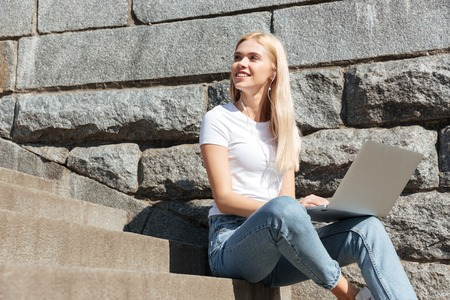 looking aside: Young pretty blonde woman sitting on stairs in the street with laptop computer and looking aside