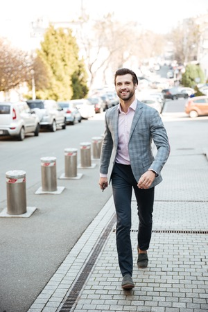 brutal: Full length portrait of a happy handsome man in a jacket walking in a city street