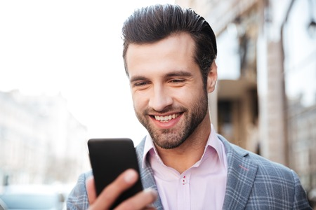 Close up portrait of a happy handsome man in jacket looking at mobile phone in a city area Фото со стока