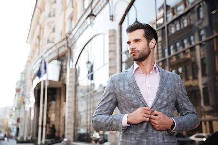 도시 지역에서 그의 재킷을 buttoning 젊은 잘 생긴 남자의 초상화 스톡 콘텐츠