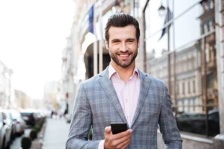 Portrait of a smiling young man in jacket holding mobile phone in a city area