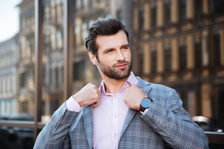 Portrait of an attractive young man straightening his jacket in a city area Stock Photo