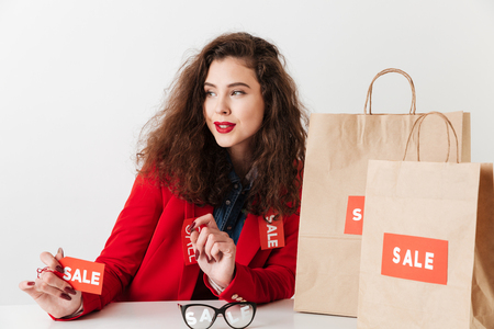 Pretty modern sale shopping woman holding sale sign while sitting with shopping bags isolated over white background