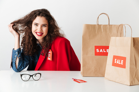 Smiling girl shopaholic sitting with paper shopping bags isolated over white background