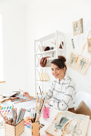 Picture of young happy lady fashion illustrator sitting at the table and drawing. Looking at camera.