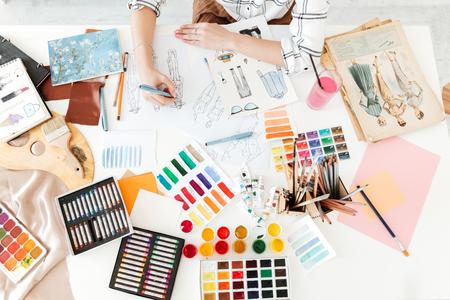 若い女性ファッション イラストレーター テーブルに座っていると、図面の平面図のトリミング写真