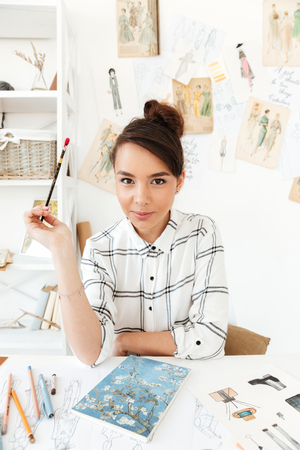 pastime: Image of young serious woman fashion illustrator sitting at the table and drawing. Looking at camera.